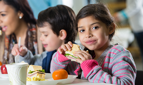 image of young girl eating lunch in cafeteria