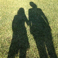 shadow of mother and daughter holding hands in a grass field